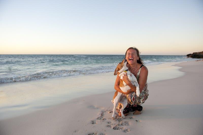 Vriendschap van vrouw en hond bij Oceaan stock foto