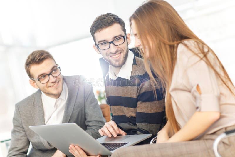 vriendschappelijk commercieel team die aan laptop werken en bedrijfskwesties bespreken stock fotografie