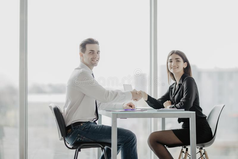 Vriendschappelijk glimlachend zakenman en onderneemsterhandenschudden over het bureau na prettige bespreking en efficiënte onderh royalty-vrije stock afbeelding