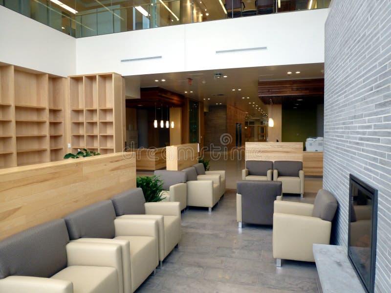 Vriendschappelijk het ziekenhuis binnenlands wachtend gebied met de moderne stoelen van het leerwapen en brandplaats stock fotografie