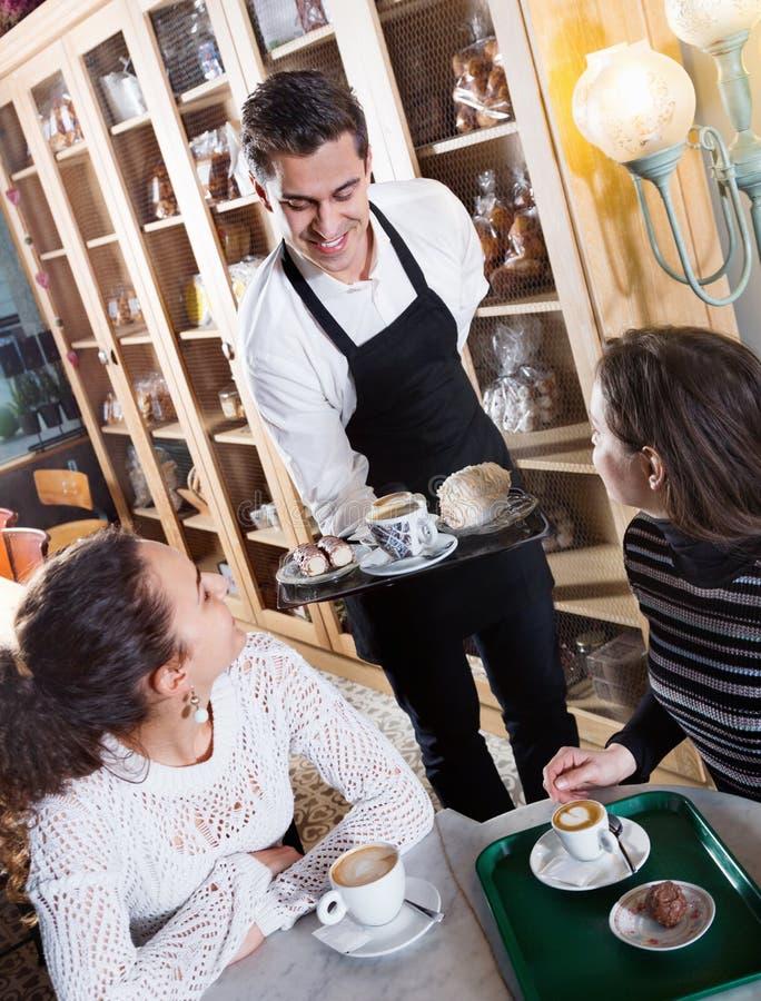 Vriendschappelijk serveerster dienend cakes en gebakje voor meisjes royalty-vrije stock afbeelding