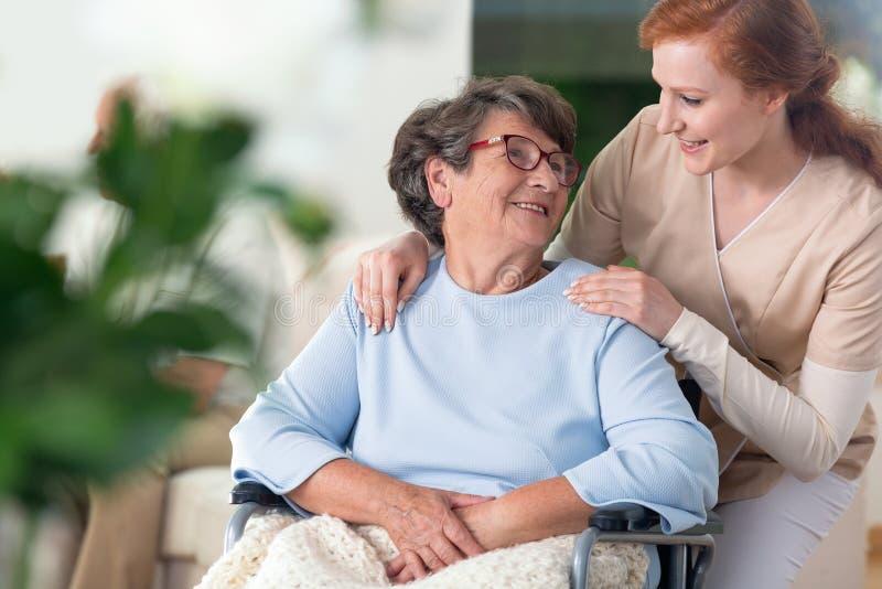 Vriendschappelijk verband tussen glimlachende verpleegster en gelukkig gehandicapt g stock foto