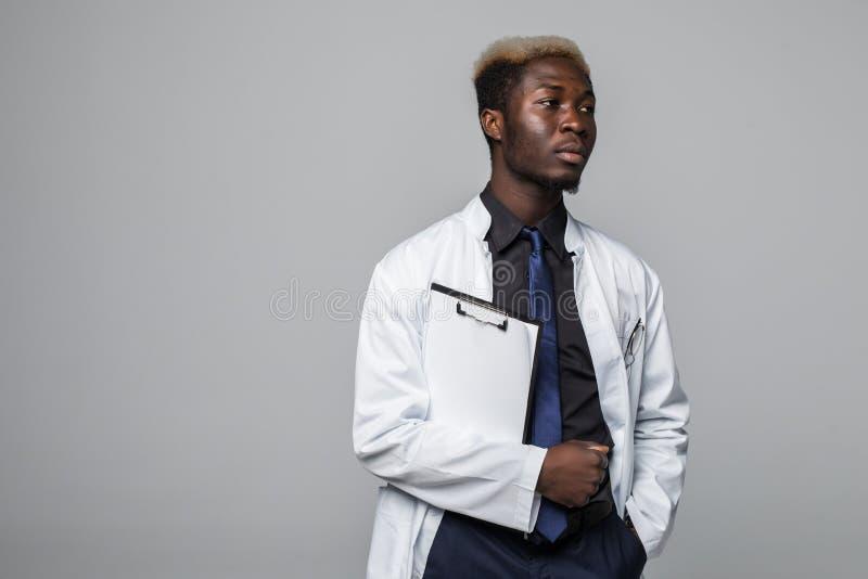 Vriendschappelijke Afro-Amerikaanse arts die een klembord houden en bij de camera op grijs glimlachen royalty-vrije stock foto's