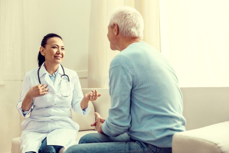 Vriendschappelijke arts die terwijl het raadplegen van teruggetrokken heer glimlachen royalty-vrije stock afbeeldingen