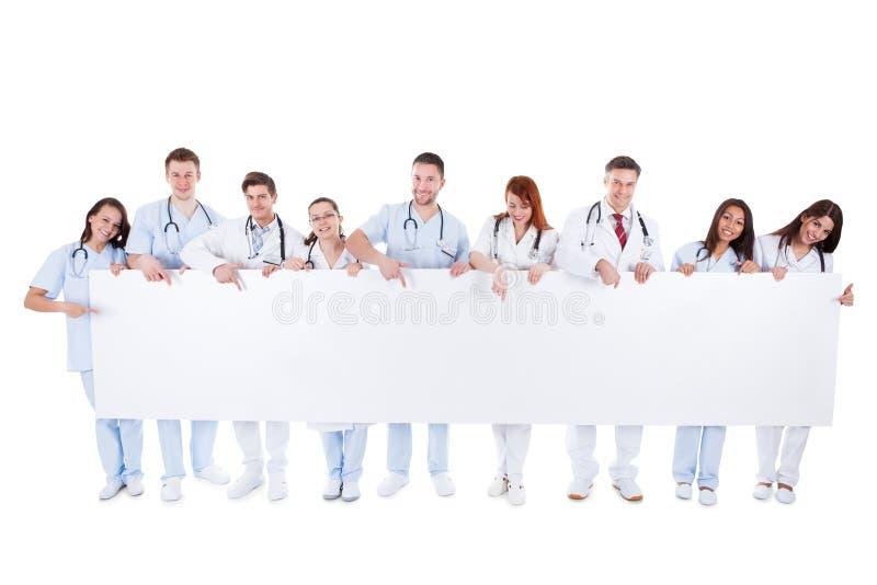 Vriendschappelijke artsen die een lege banner houden royalty-vrije stock afbeelding