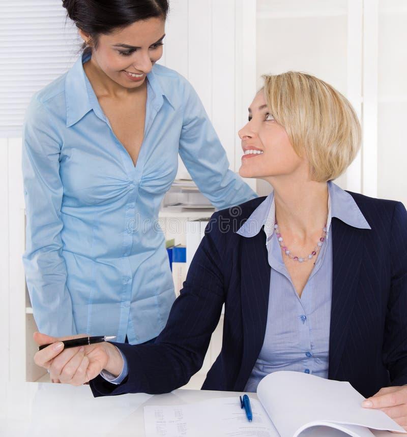 Vriendschappelijke atmosfeer op het werk: glimlachende onderneemster twee stock afbeelding