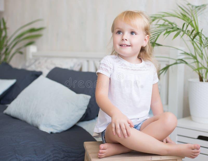 Vriendschappelijke blootvoetse meisjezitting op een kruk stock afbeeldingen