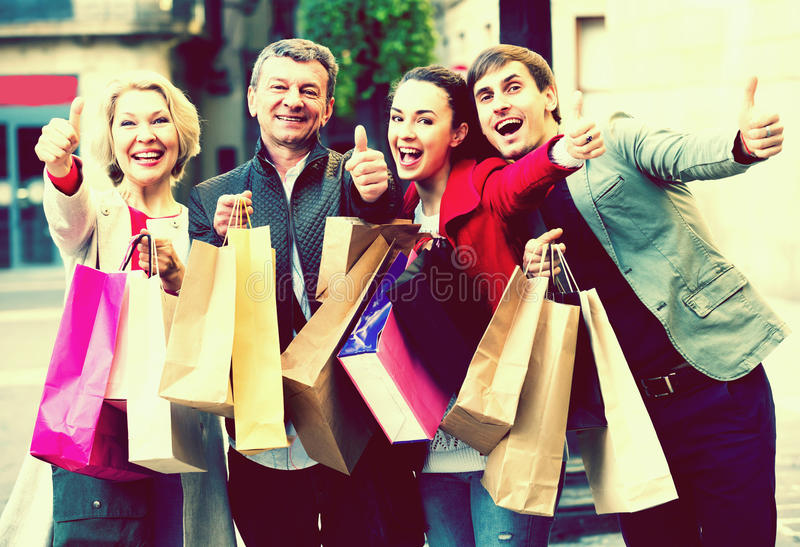 Vriendschappelijke familie van vier met het winkelen zakken stock afbeelding