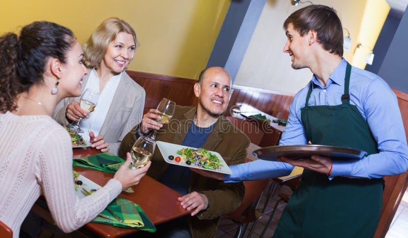 Vriendschappelijke glimlachende kelner die orde nemen bij lijst van mensen royalty-vrije stock fotografie
