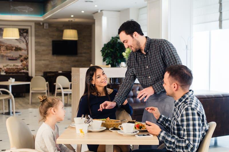 Vriendschappelijke glimlachende kelner die orde samen nemen bij lijst van familie die diner hebben stock foto's