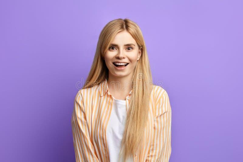 Vriendschappelijke glimlachende mooie die blondevrouw op blauwe achtergrond wordt geïsoleerd royalty-vrije stock afbeelding