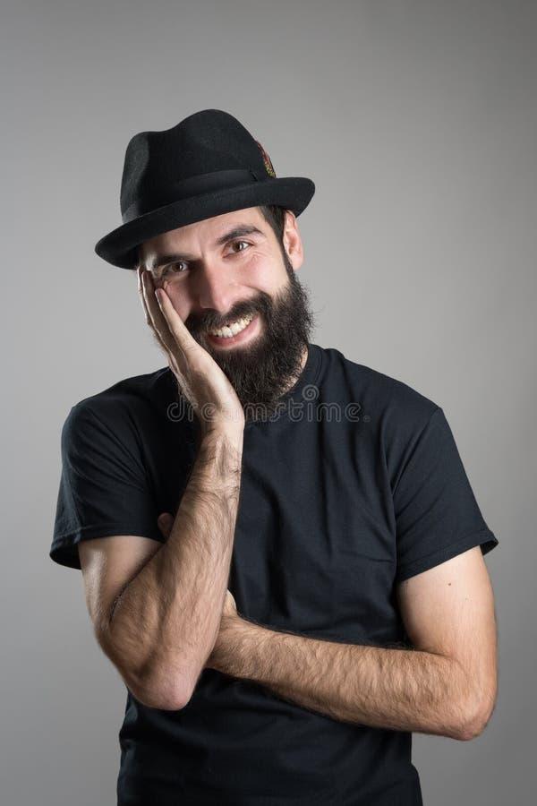 Vriendschappelijke het glimlachen gebaarde hipster die zwarte t-shirt en hoed met hoofd dragen die op zijn hand rusten stock afbeeldingen