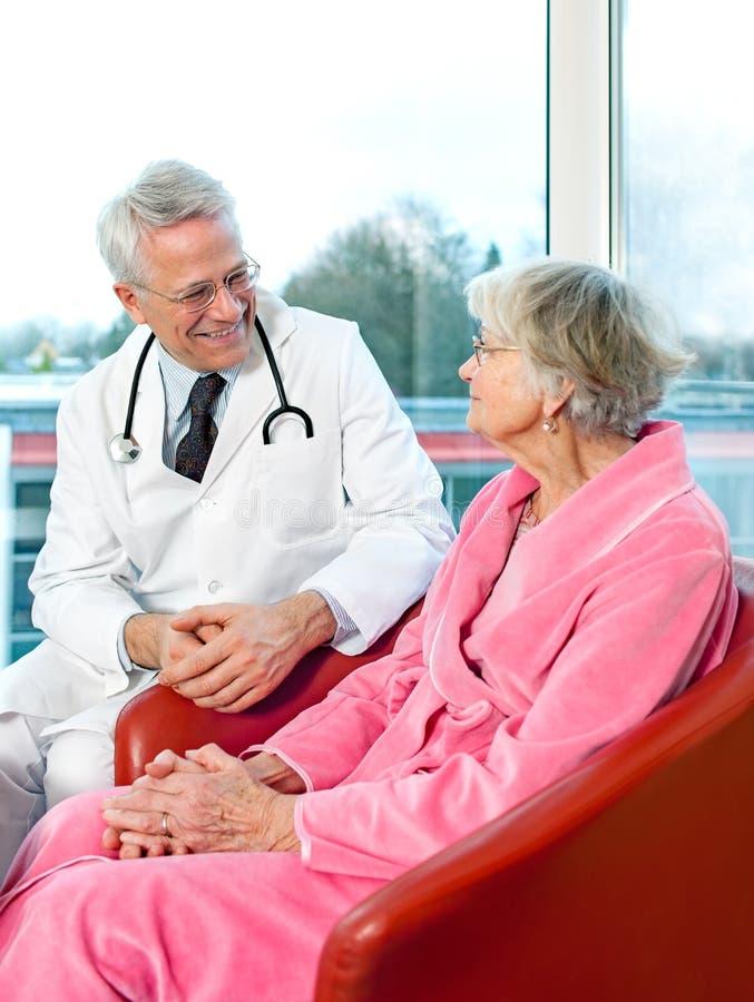 Vriendschappelijke hogere mannelijke arts die aan een patiënt babbelen stock afbeeldingen