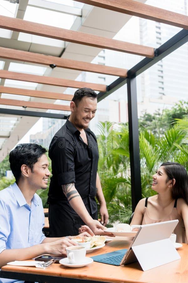 Vriendschappelijke jonge kelner die met de cliënten in openlucht spreken stock foto