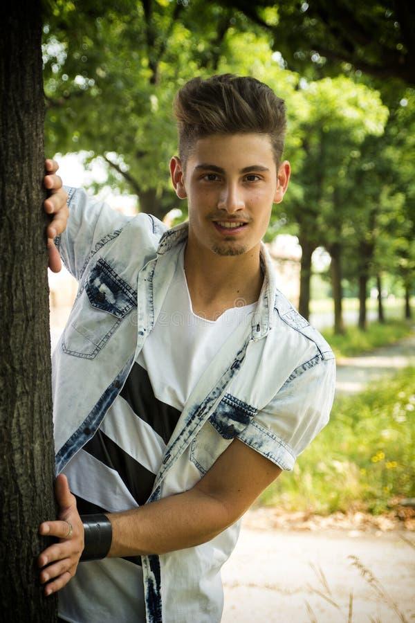 Vriendschappelijke knappe jonge mens achter boom het glimlachen stock afbeeldingen