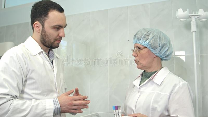 Vriendschappelijke mannelijke arts die aan de bloedmonsters van de verpleegstersholding spreken stock afbeeldingen