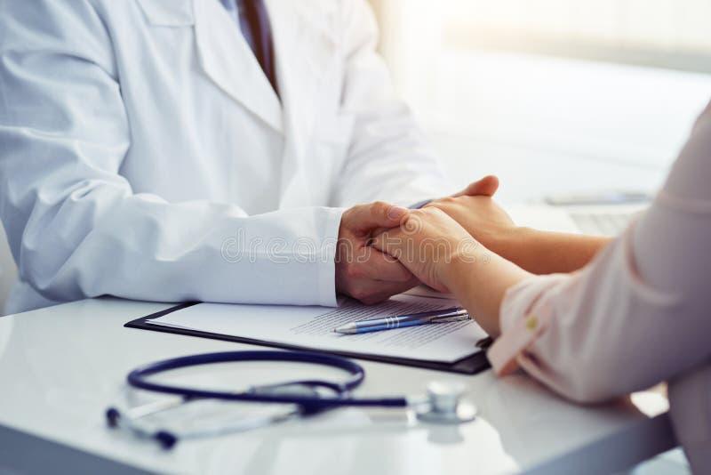 Vriendschappelijke mannelijke arts die de patiënt geruststellen en zijn handen houden stock afbeeldingen