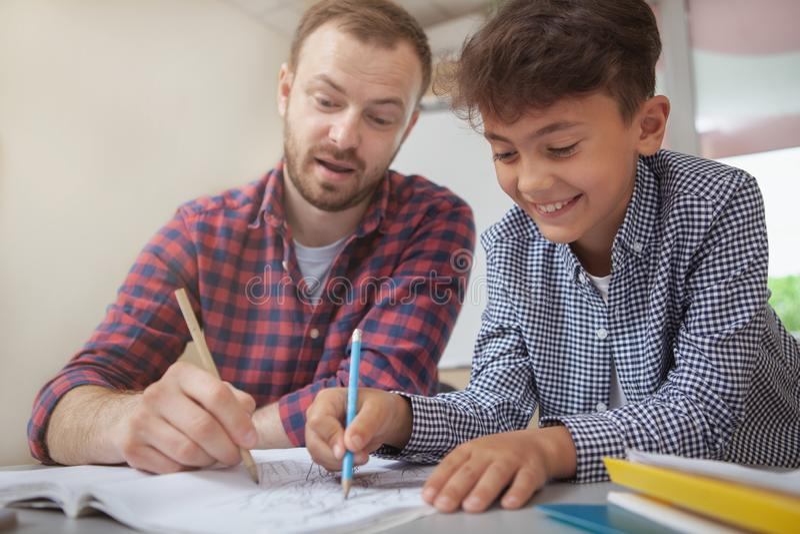 Vriendschappelijke mannelijke leraar die zijn kleine student helpen royalty-vrije stock foto's
