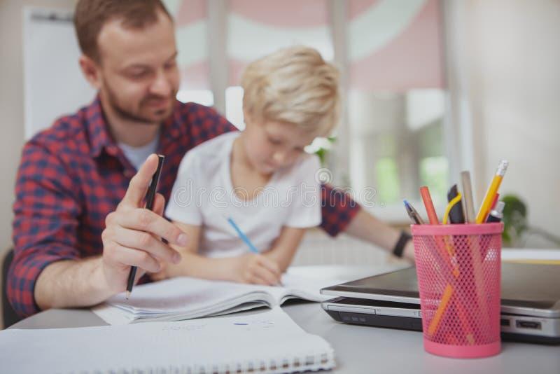 Vriendschappelijke mannelijke leraar die zijn kleine student helpen royalty-vrije stock afbeelding