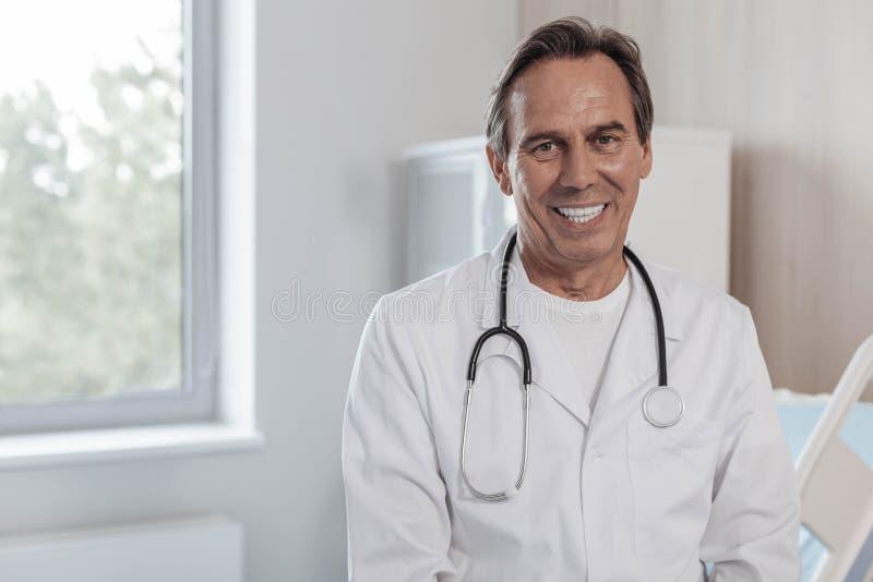 Vriendschappelijke medische arbeider die ruim in camera grijnzen stock foto