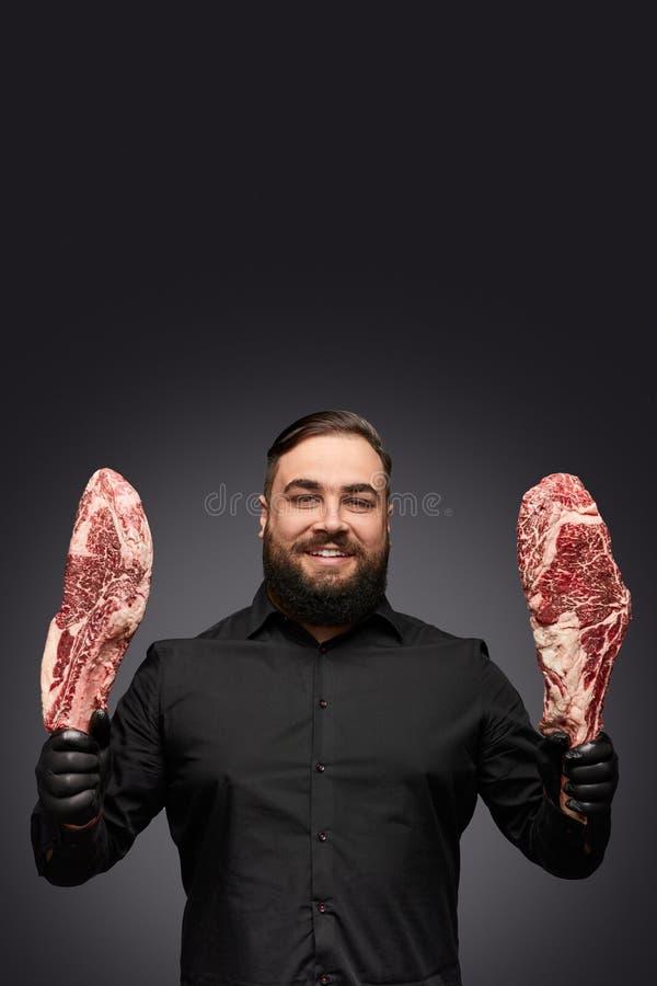 Vriendschappelijke mens die vers vlees tonen stock foto
