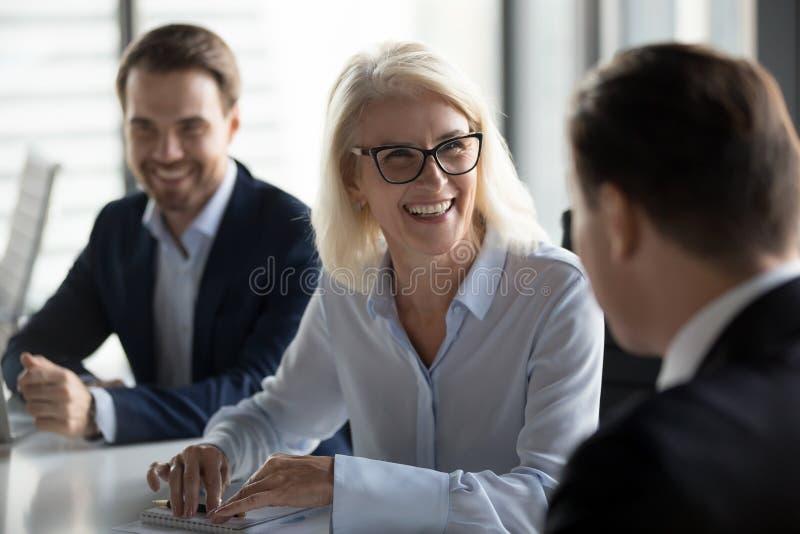 Vriendschappelijke midden oude vrouwelijke leider die bij groeps commerciële vergadering lachen royalty-vrije stock afbeeldingen