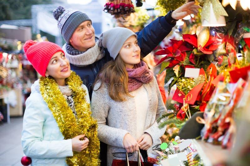 Vriendschappelijke ouders met tiener bij teller met Poinsettia royalty-vrije stock afbeelding