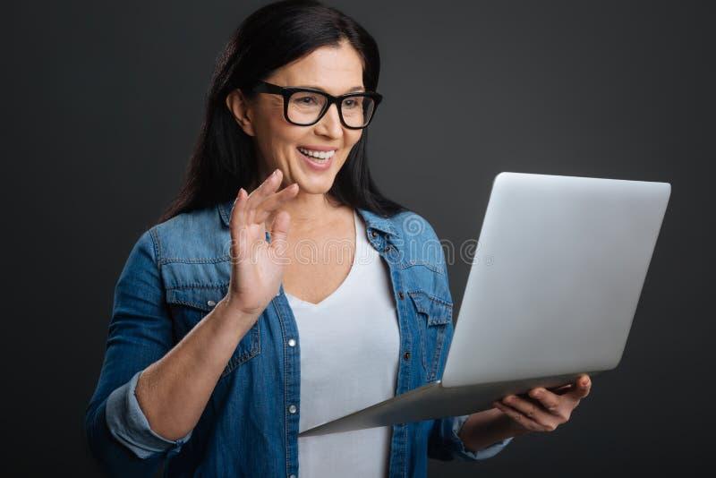 Vriendschappelijke positieve dame die moderne technologie voor mededeling gebruiken stock fotografie