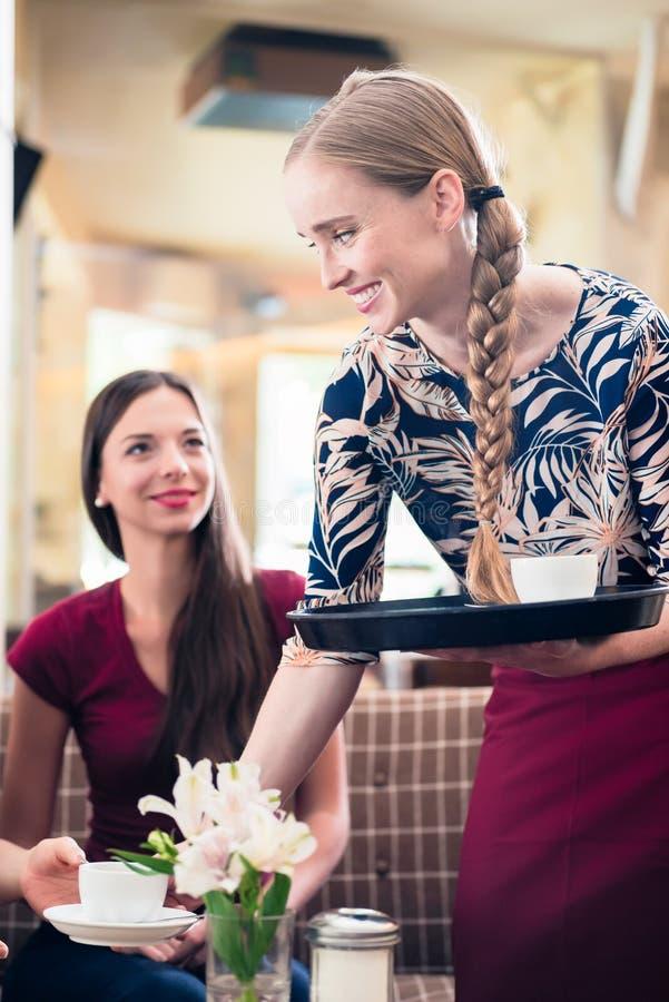 Vriendschappelijke serveerster dienende koffie in een modieus restaurant stock afbeeldingen