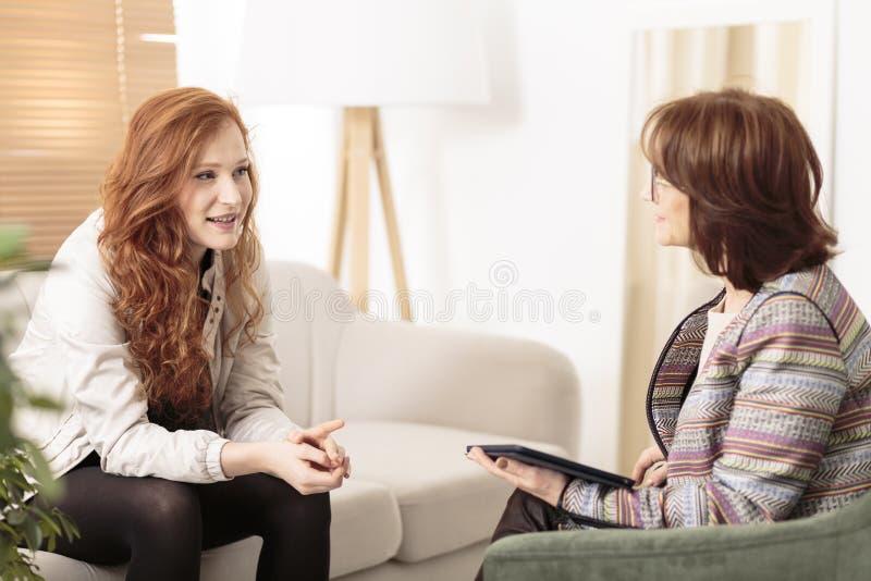 Vriendschappelijke therapeut ondersteunend roodharige vrouw royalty-vrije stock afbeeldingen