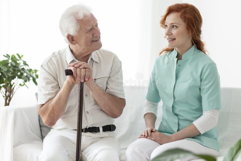 Vriendschappelijke verpleegster die met glimlachend bejaarde met het lopen sti spreken stock foto's
