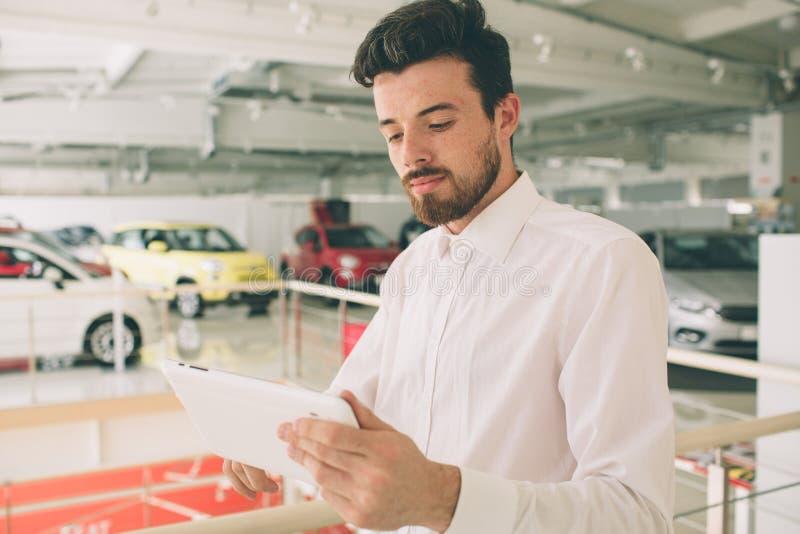 Vriendschappelijke voertuigverkoper die nieuwe auto's voorstellen bij toonzaal De foto van jonge mannelijke adviseur die nieuwe a stock afbeeldingen