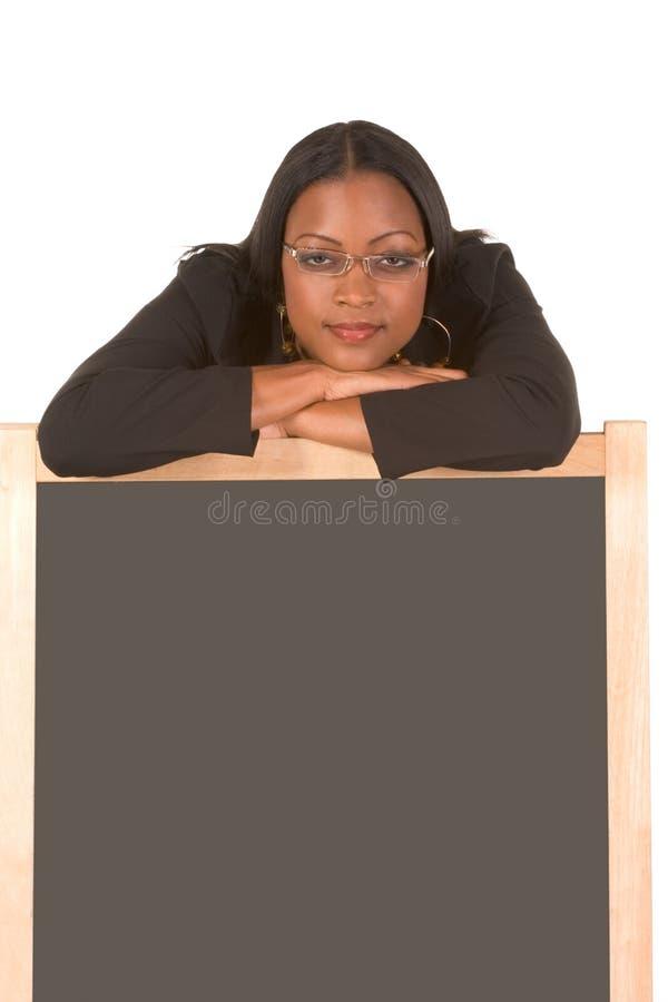 Vriendschappelijke volwassen student die op schoolbord leunt royalty-vrije stock foto's