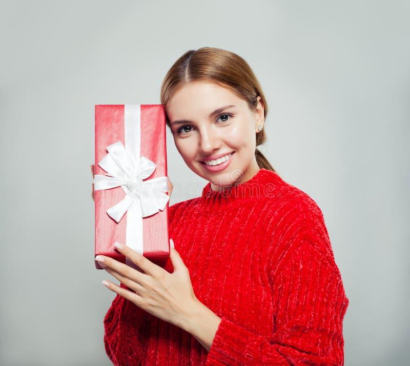 Vriendschappelijke vrouw die giftdoos tonen en op witte achtergrond glimlachen stock afbeeldingen
