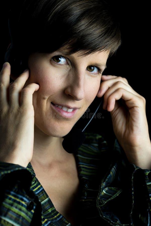 Vriendschappelijke vrouw die hoofdtelefoon met hoofdtelefoons met behulp van royalty-vrije stock fotografie