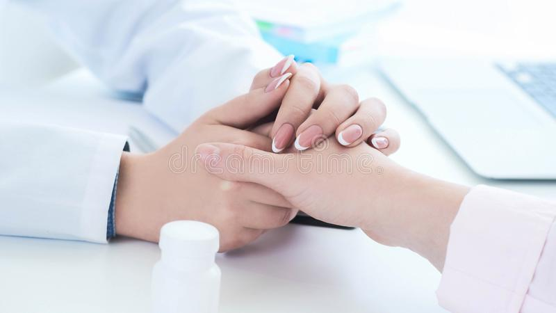 Vriendschappelijke vrouwelijke artsenhanden die geduldige handzitting houden bij het bureau voor aanmoediging, empathie, het toej royalty-vrije stock foto