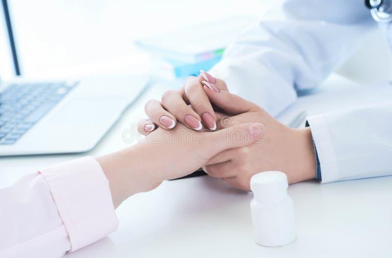 Vriendschappelijke vrouwelijke artsenhanden die geduldige handzitting houden bij het bureau voor aanmoediging, empathie, het toej stock afbeeldingen