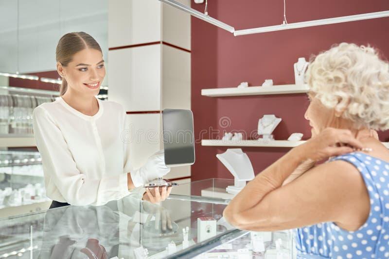 Vriendschappelijke vrouwelijke verkoper die hogere dame onderhouden bij juwelenwinkel stock foto's