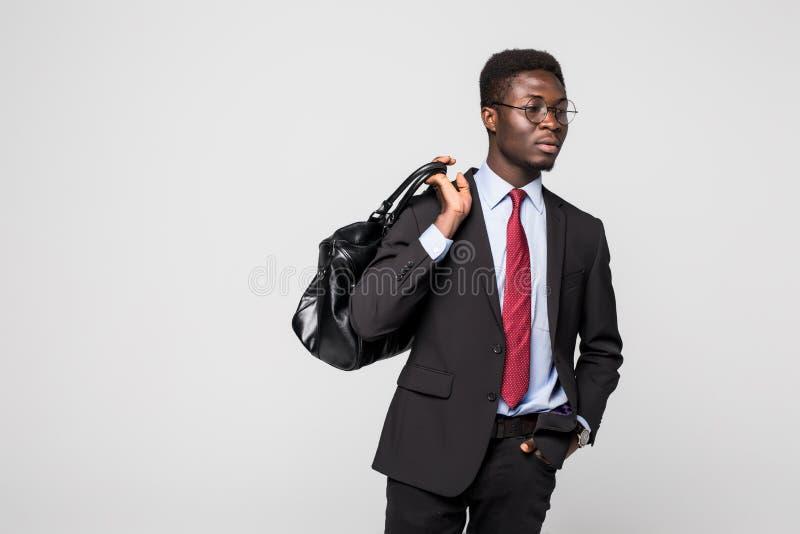 Vriendschappelijke zwarte zakenman die met zijn zak die en gelukkig op grijze achtergrond lopen glimlachen royalty-vrije stock afbeelding