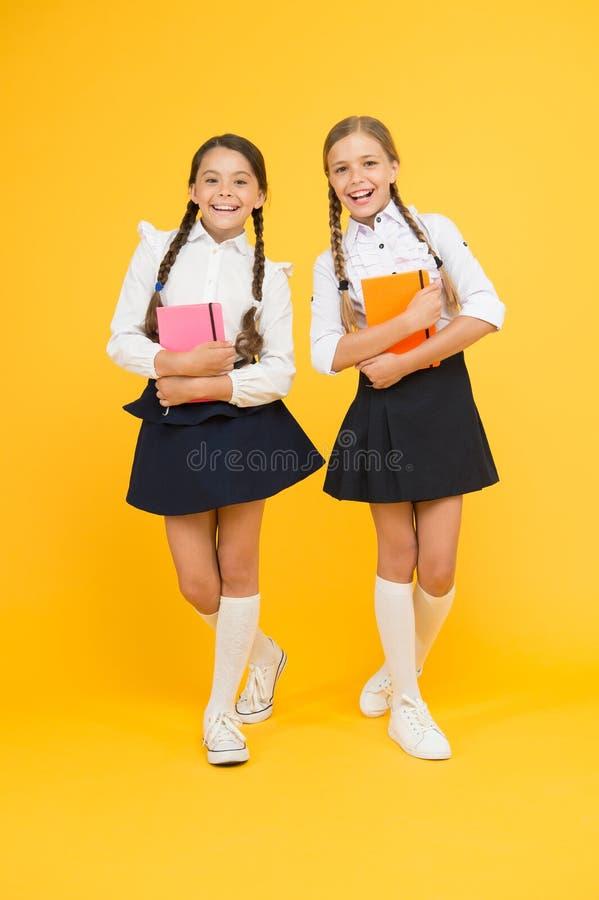 Vriendschapsdoelstellingen Leuke schoolmeisjes met boeken Eerste dag op school Klasgenoten van jonge geitjes de beste vrienden Sc stock afbeeldingen