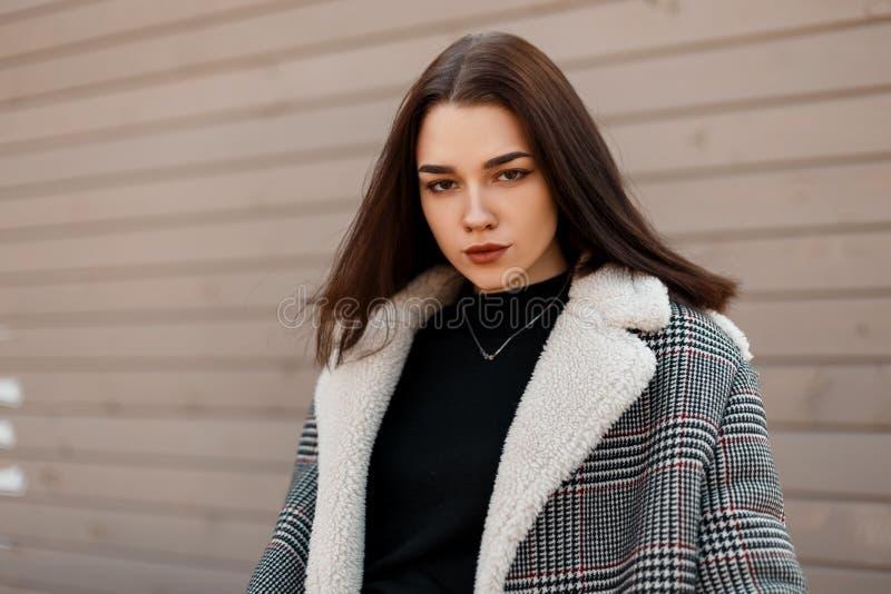 Vrij aantrekkelijke jonge vrouw met natuurlijke samenstelling in een geruit grijs in jasje met administratief royalty-vrije stock foto