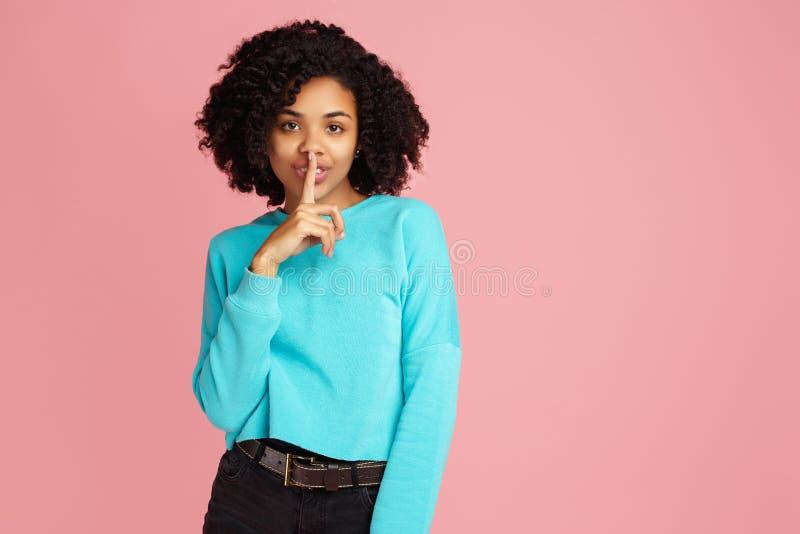 Vrij Afrikaanse Amerikaanse jonge vrouw in de toevallige wijsvinger van de kledingsholding op lippen en het vragen om stilte over stock foto's