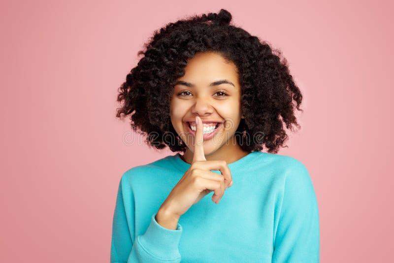 Vrij Afrikaanse Amerikaanse jonge vrouw in de toevallige wijsvinger van de kledingsholding op lippen en het vragen om stilte over royalty-vrije stock foto