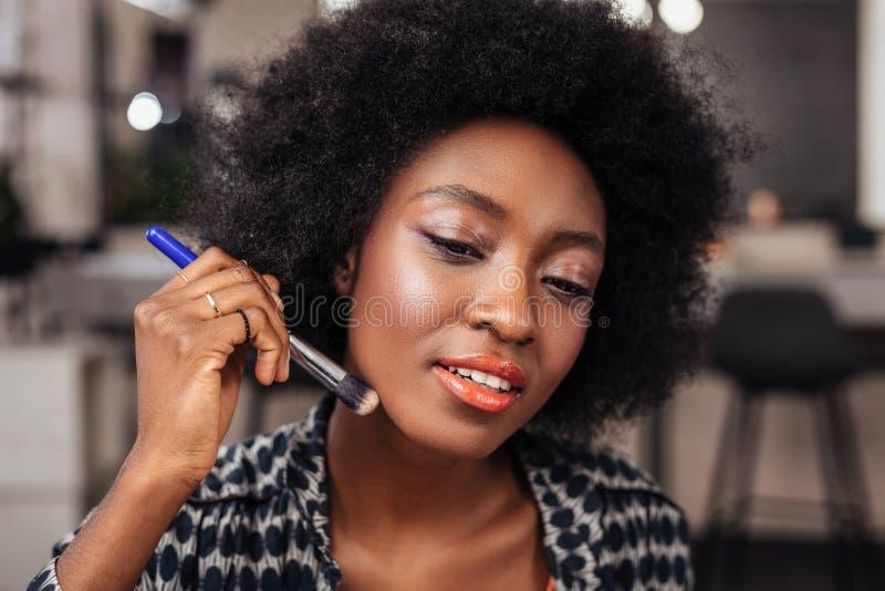 Vrij Afrikaanse Amerikaanse vrouw die met krullend haar een nieuwe camouflagestift op haar gezicht zetten royalty-vrije stock afbeeldingen
