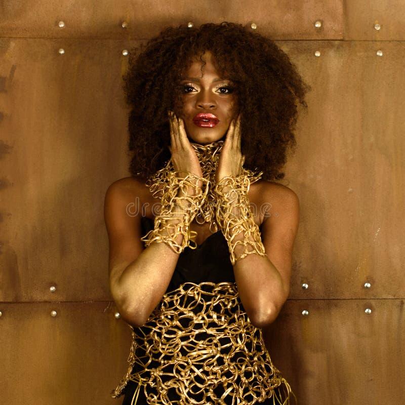 Vrij Afrikaanse vrouw met zwart krullend haar en gouden make-up, toebehoren, die de handen van de cameraholding dichtbij gezicht  royalty-vrije stock fotografie