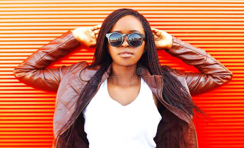Vrij Afrikaanse vrouw in zonnebril en jasje bij stad over rood royalty-vrije stock afbeeldingen