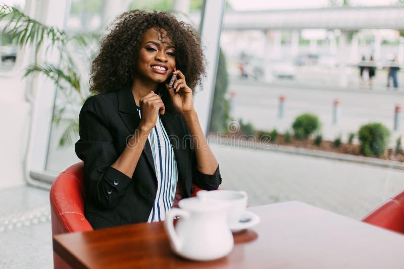 Vrij Afro-Amerikaanse meisjesbesprekingen op de mobiele telefoon kop van verse espresso met speld hierboven teken, mening van stock afbeelding