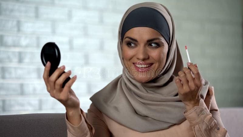 Vrij Arabische huisvrouw die lipgloss toepassen, die in kleine spiegel, schoonheid, stijl kijken royalty-vrije stock afbeelding