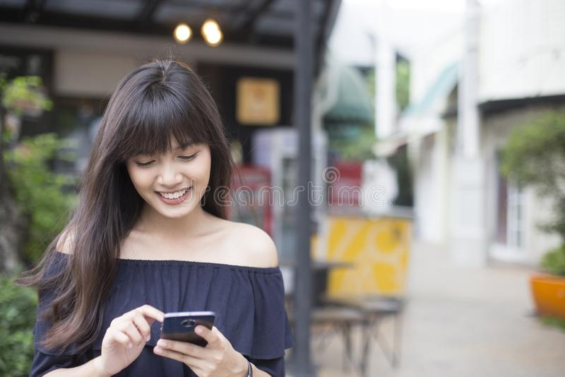 Vrij Aziatisch meisje gelukkig met smartphone stock afbeelding