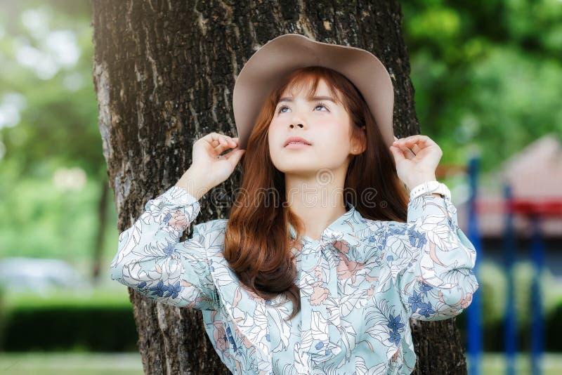 Vrij Aziatisch meisje in uitstekende kleding die tegen op de boom en het ontspannen leunen stock afbeeldingen